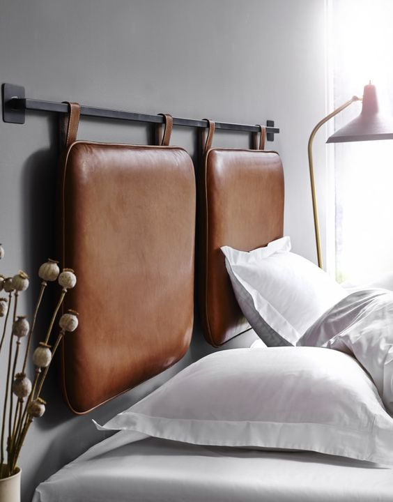 a contemporary bed with a leather hanging headboard in brown is a chic and stylish idea to try