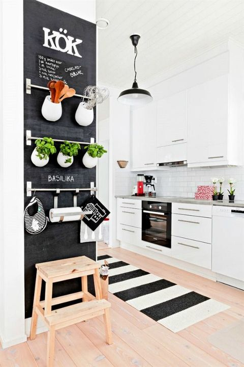 a Scandinavian kitchen in a monochromatic color scheme, with a chalkboard herb wall with railings