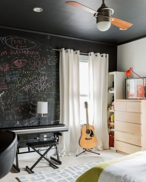 a small bedroom for a creative person with a chalkboard wlal for art and messages, with all white everything to fill the space with light