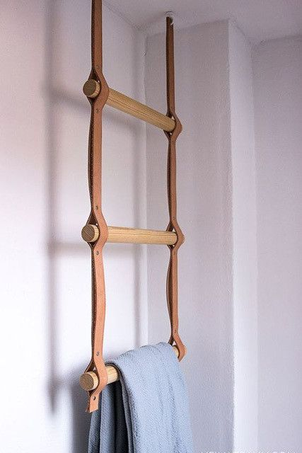 a towel holder in the bathroom made of leather straps and wooden sticks is a stylish modern accessory to make