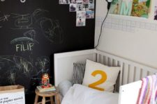 24 a small yet cute kid's space with a chalkboard accent wall decorated with art and some family pics, with open shelves and a cozy bed