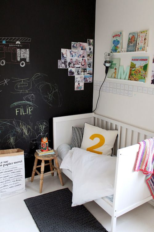 a small yet cute kid's space with a chalkboard accent wall decorated with art and some family pics, with open shelves and a cozy bed