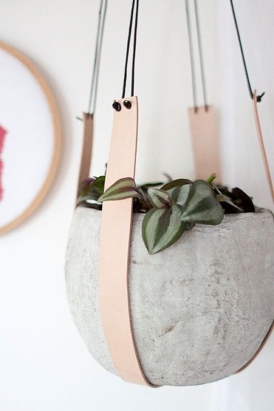 a concrete planter suspended using leather straps is a stylish and ultra-modern idea to try