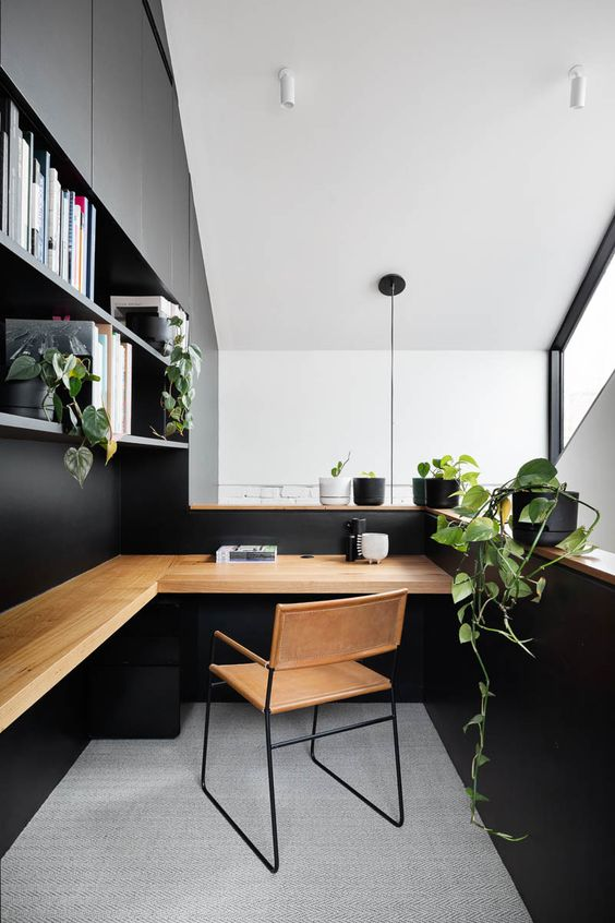 a small minimalist home office with a monochromatic color scheme, a wooden desk and a leather chair plus greenery