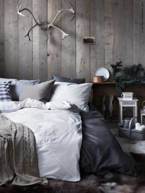 a Nordic chalet bedroom with a reclaimed wood wall, grey and white bedding, candle lanterns and antlers on the wall