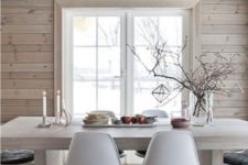 a Nordic chalet dining room done with whitewashed wood, with a white lamp and chairs plus some candles
