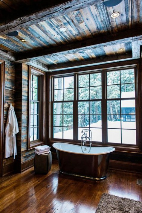 a beautiful and simple chalet bathroom clad with rich stained weathered wood, with a metal tub and much light through windows