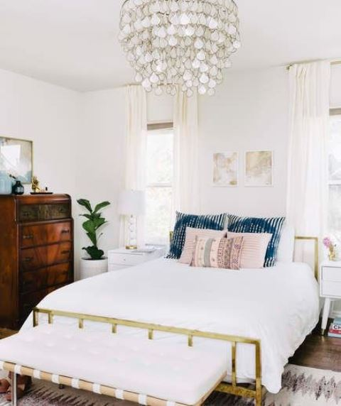 a beautiful beach bedroom with a gold bed, an upholstered bench, printed bedding, a mother of pearl chandelier and a dark stained dresser