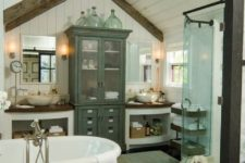 a beautiful neutral farmhouse bathroom with lots of furniture, a shower space, a vintage-inspired tub and wooden beams on the ceiling