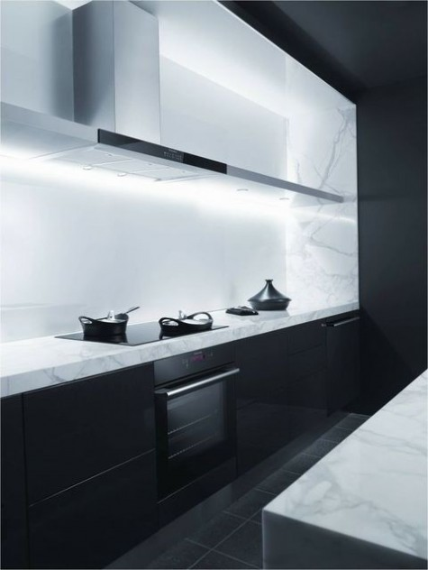 a black minimalist kitchen with white stone countertops and a sleek white backsplash plus a long metal hood
