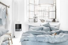 a boho coastal bedroom done in white, with blue bedding, a paper lamp, wooden furniture, baskets and some blue textiles