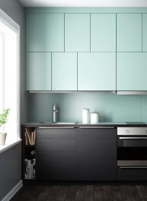 a bold minimalist kitchen with mint upper and black lower cabinets and a bold backsplash to infuse your home with color
