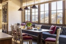 a bright and elegant chalet dining space with a grey sofa, colorful chairs, pendant lamps and a vintage table