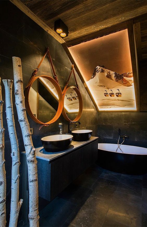 a chalet bathroom clad with dark tiles, with a black tub and sinks, wood frame mirrors and birchwood