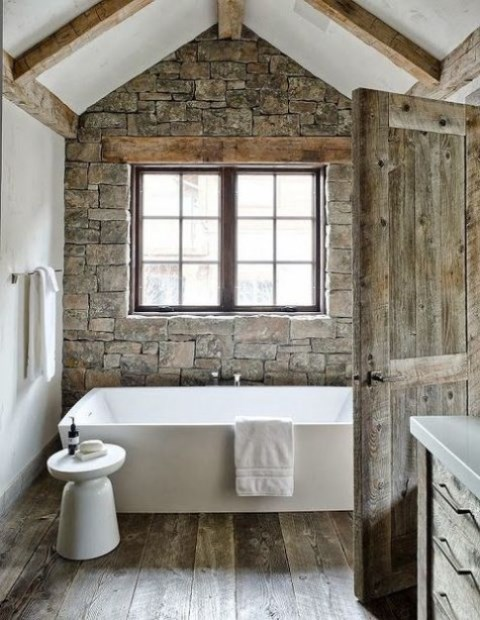 a chalet bathroom with white walls and a stone one, wooden beams, a modern tub and stool and a reclaimed wooden door