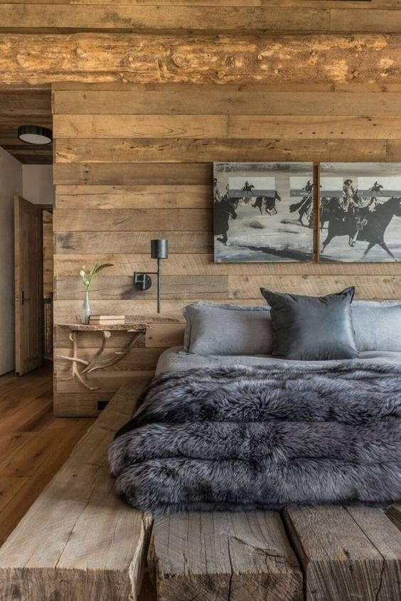 a chalet bedroom with a rough wood platform bed, antler and wood nightstands and artworks