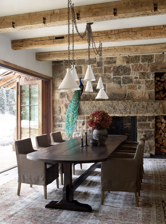 a chalet dining room with dark vintage furniture, a stone clad fireplace, pendant lamps and doors that are opened