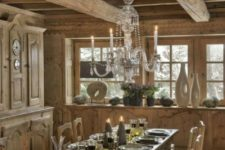 a chalet dining space all done with wood, with vintage carved furniture, a crystal chandelier and some candles