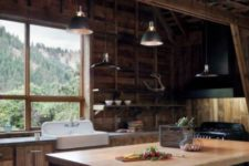 a chalet kitchen clad with reclaimed wood, with a alrge black kitchen island, vintage metal lamps and a large window