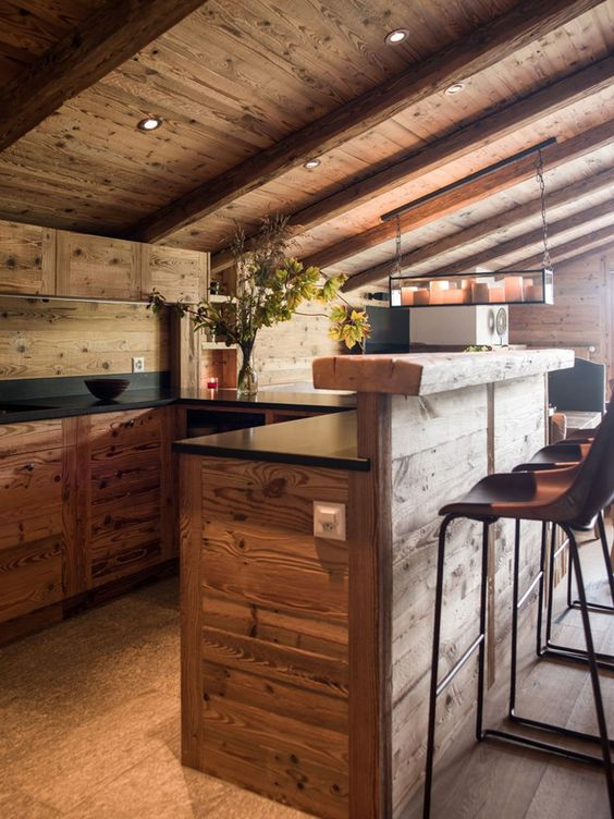 a chalet kitchen done with wooden cabinets and a kitchen island with a raised eating top, built-in lights and black countertops