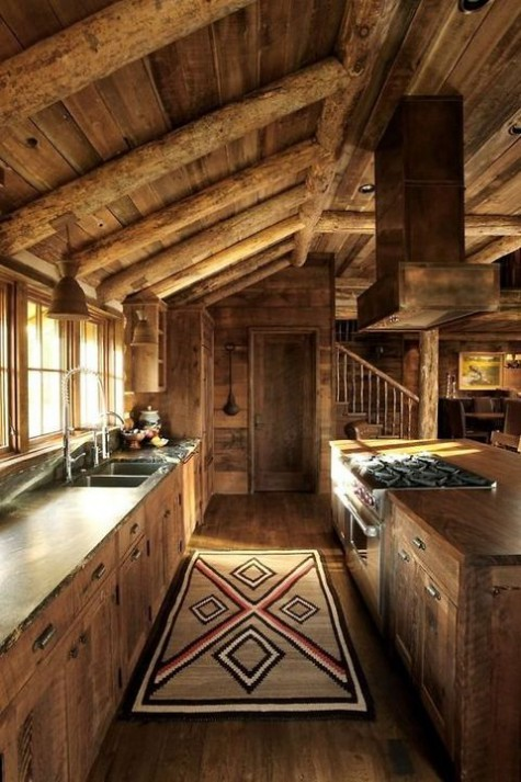 a chalet kitchen fully clad with wood, with wooden beams, weathered wood cabinets, a boho rug and porcelain pendant lamps