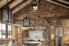 a chalet kitchen with a stone clad wall, wooden cabinets and a kitchen island, pendant lamps and skylights is very cozy