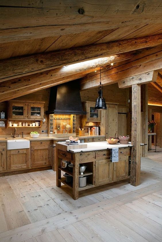 a chalet kitchen with wooden beams and a skylight, a wooden kitchen island and cabines, a black hood and lamps