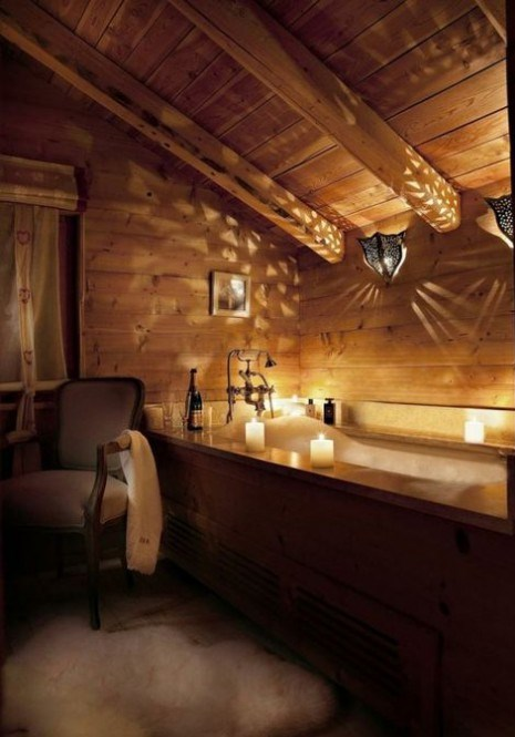 a chic chalet bathroom clad with light-colored wood completely, with a wood clad tub, refined furniture and lights and candles