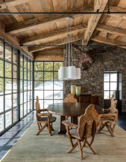 a chic chalet dining room with a stone wall, a faux deer head, a vintage table and rustic chairs plus a glazed wall