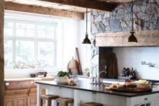 a chic chalet kitchen with a stone wall with built-in appliances, a large kitchen island, metal pendant lamps and a large window