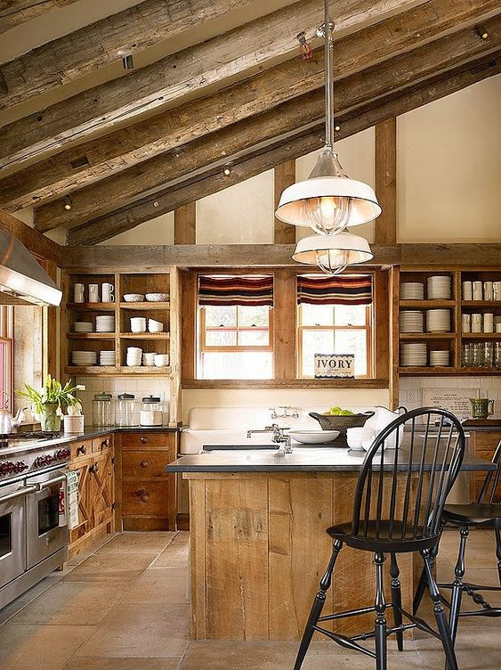 a chic chalet kitchen with wooden beams, wooden cabients and a kitchen island, stone countertops and pendant lamps