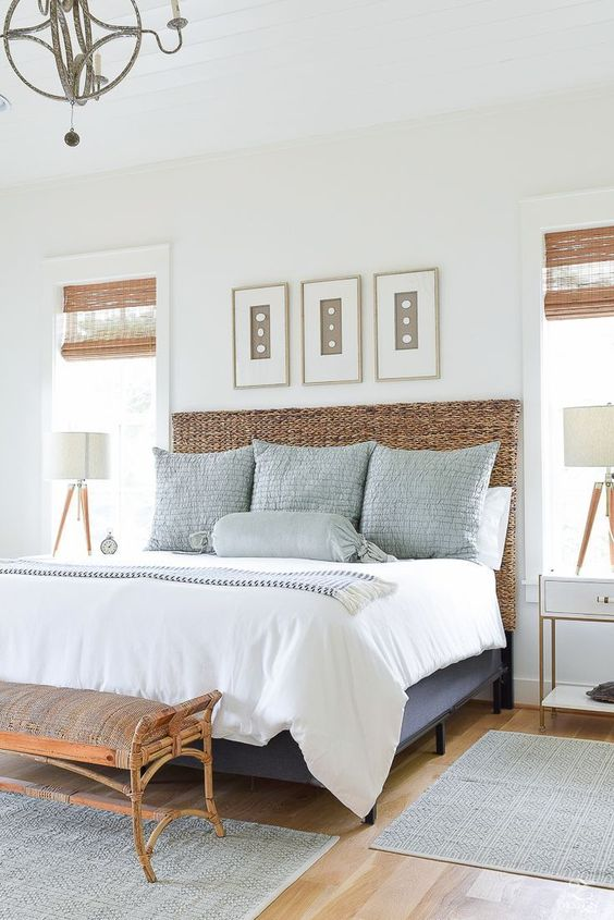 a chic coastal bedroom with a blue bed with a wicker headboard, a rattan bench, a wall gallery with seashells and a vintage chandelier