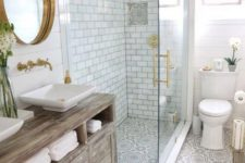 a chic farmhouse bathroom with neutral and printed tiles, a shabby chic wooden vanity, a gold frame mirror and cool lighting
