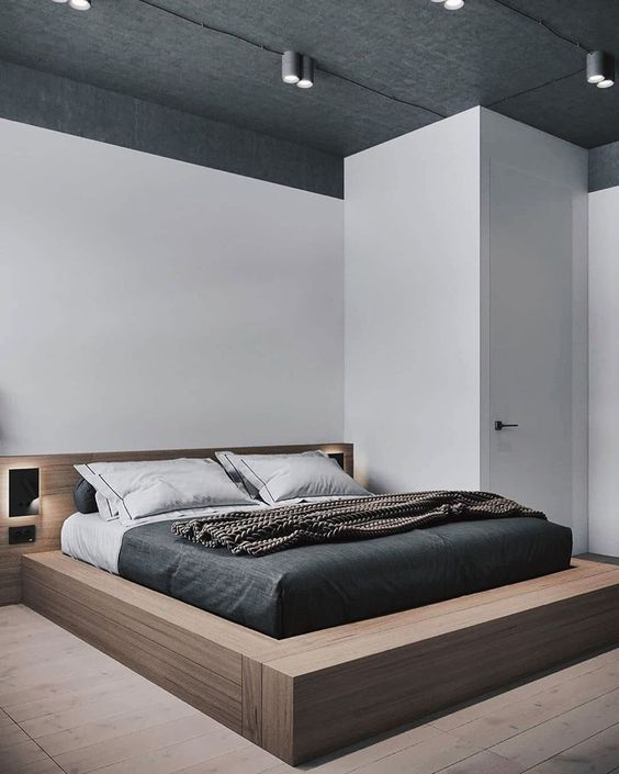 a chic minimal bedroom with a platform plywood bed with built-in lights, lights on the ceiling and monochromatic bedding