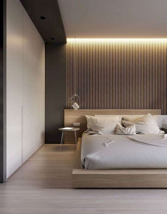 a chic minimal bedroom with a wooden bed, a wooden slabs, built-in lights, sleek storage space and sconces