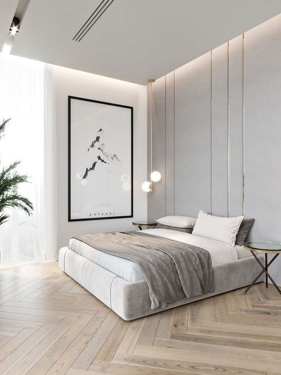 a chic minimalist bedroom in neutrals, with built-in lights, a statement artwork, pendant lamps and potted plants