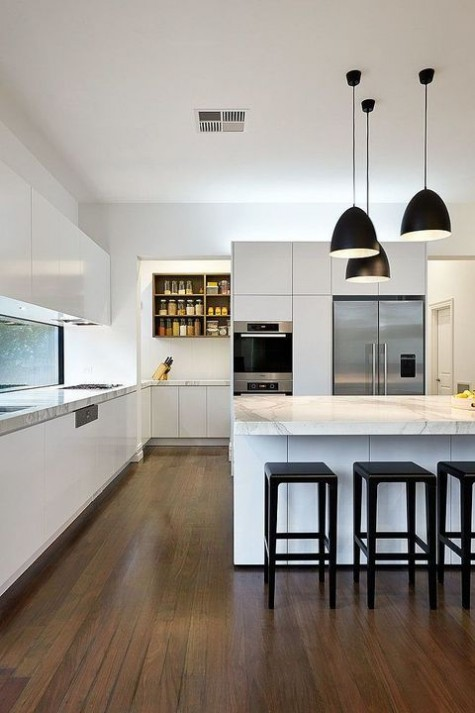 a chic minimalist kitchen in white, with sleek cabinets, marble countertops and black pendant lamps and stools