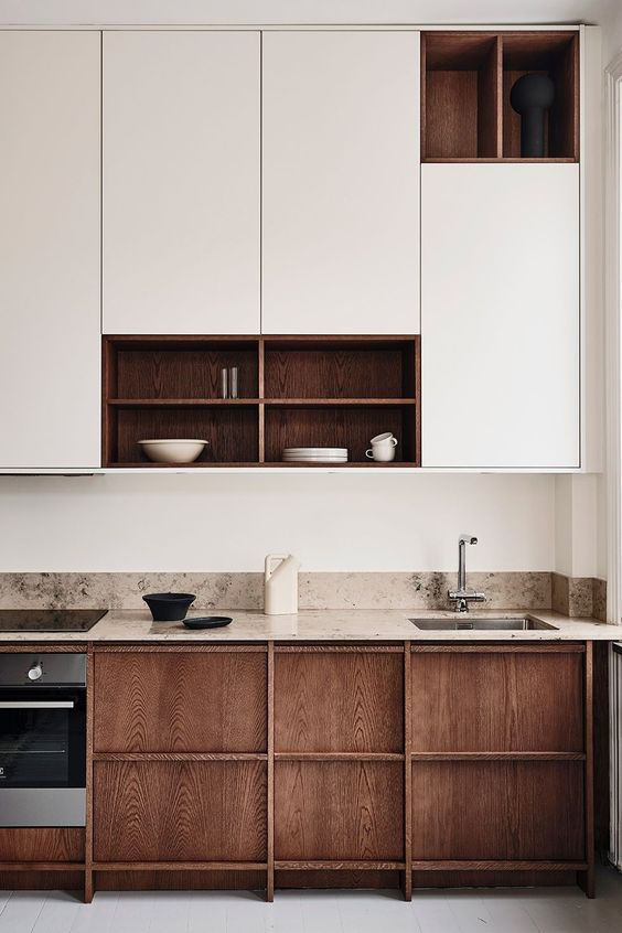 a chic minimalist kitchen with neutral cabinets, wooden ones and a tan stone countertop plus backsplash for a warmer look