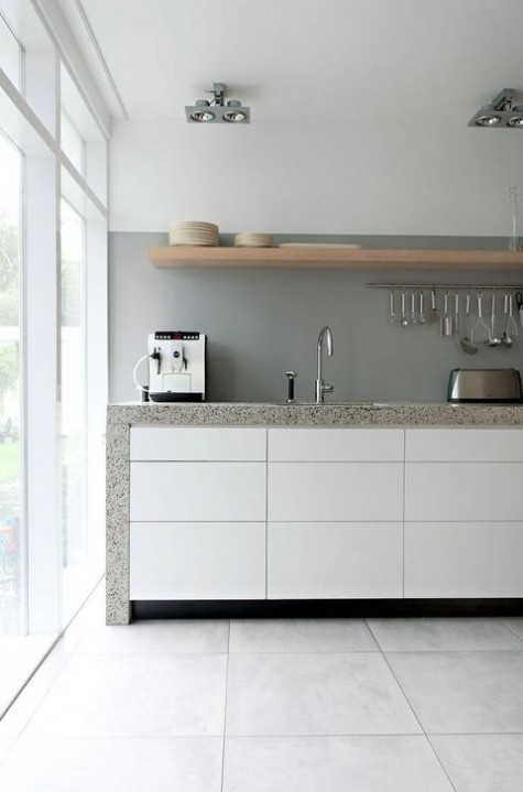 a chic minimalist kitchen with sleek white cabinets, a concrete backsplash and grey stone countertops plus a wooden shelf