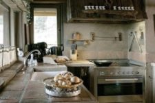a chic modern chalet kitchen with reclaimed wood cabinets, tile countertops, a wooden ceiling and hood plus built-in lights