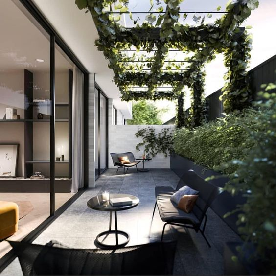 a chic modern patio with a long black planter along the wall, black garden furniture and much greenery climbing up the space