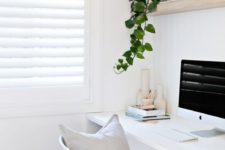 a clean minimalist home office nook with a beadboard wall, an open shelf, a white desk and a potted plant