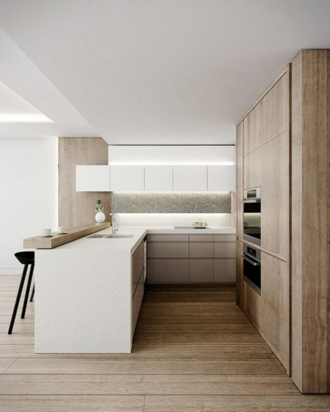 a clean ultra minimalist kitchen with sleek white and wooden cabinets, a wooden raised countertop, built in lights and a concrete backsplash