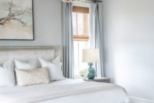 a coastal bedroom in light and pastel blues, with a chic bed and bench, a wood bead chandelier, blue textiles and an artwork