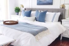 a coastal bedroom with a grey upholstered bed, blue and white printed textiles, a sea artwork, a stool and potted plants
