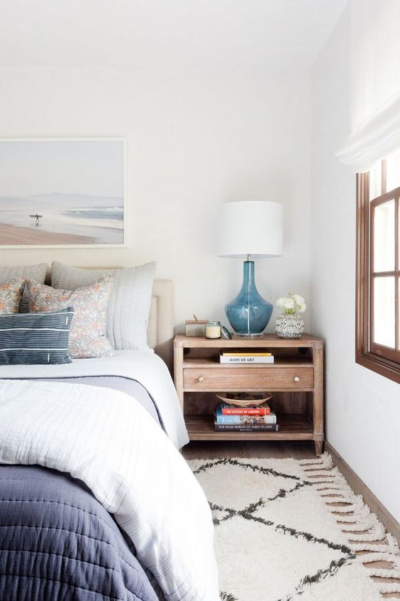 a coastal bedroom with white walls, a wooden floor and furniture, blue printed bedding, a sea artwork and a blue lamp