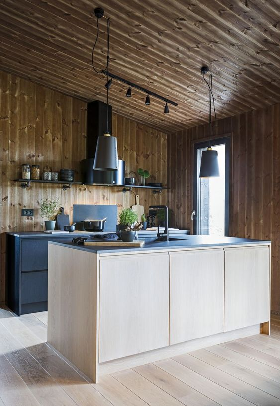 a contemporary chalet kitchen all clad with wood, with black metal cabinets and a plywood kitchen island, black countertops and a black hood