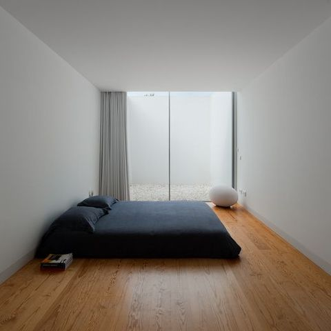 a cool minimalist bedroom with a large bed with black bedding, a catchy soft egg stool and a large window