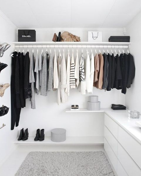 a cool minimalist white closet with a holder for hangers, a sideboard, open shelves and boxes