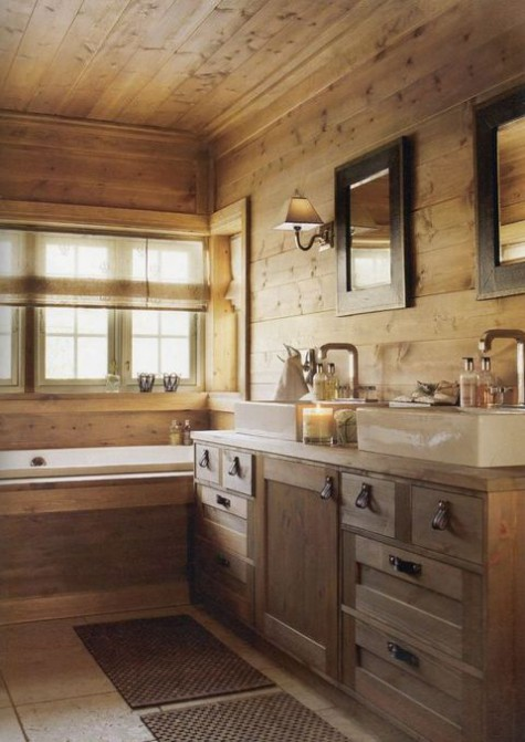a cozy chalet bathroom clad with light-colored wood, with a large vanity and a wood clad bathtub, windows and mirrors